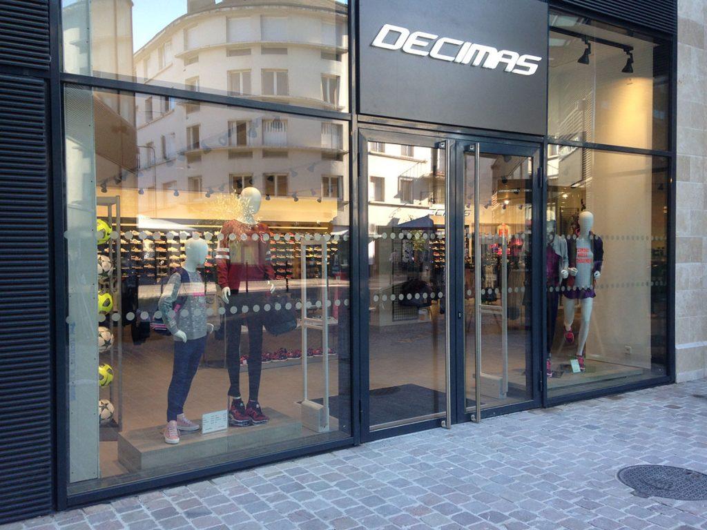 Pose d'une bande adhésive dépolie sur vitrine de magasin pour une mise aux normes PMR