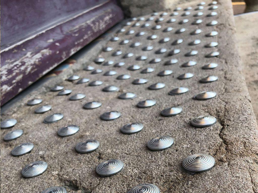 Pose extérieure de clous podotactiles sur marches